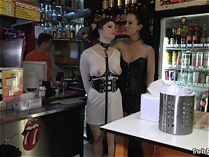 mistress in leather dominates slave in public